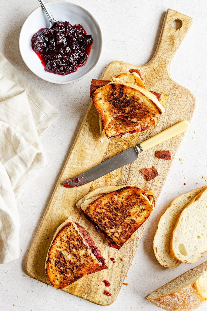 Vegan bacon, cranberry and camembert cheese toastie served up on a wooden board