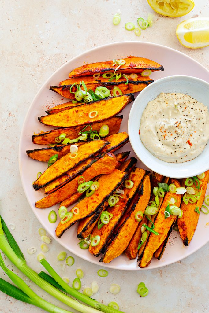 Spicy vegan sweet potato wedges served with creamy tahini and yoghurt dip