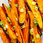 Close up of some vegan spicy sweet potato wedges on a side plate, topped with chopped spring onion