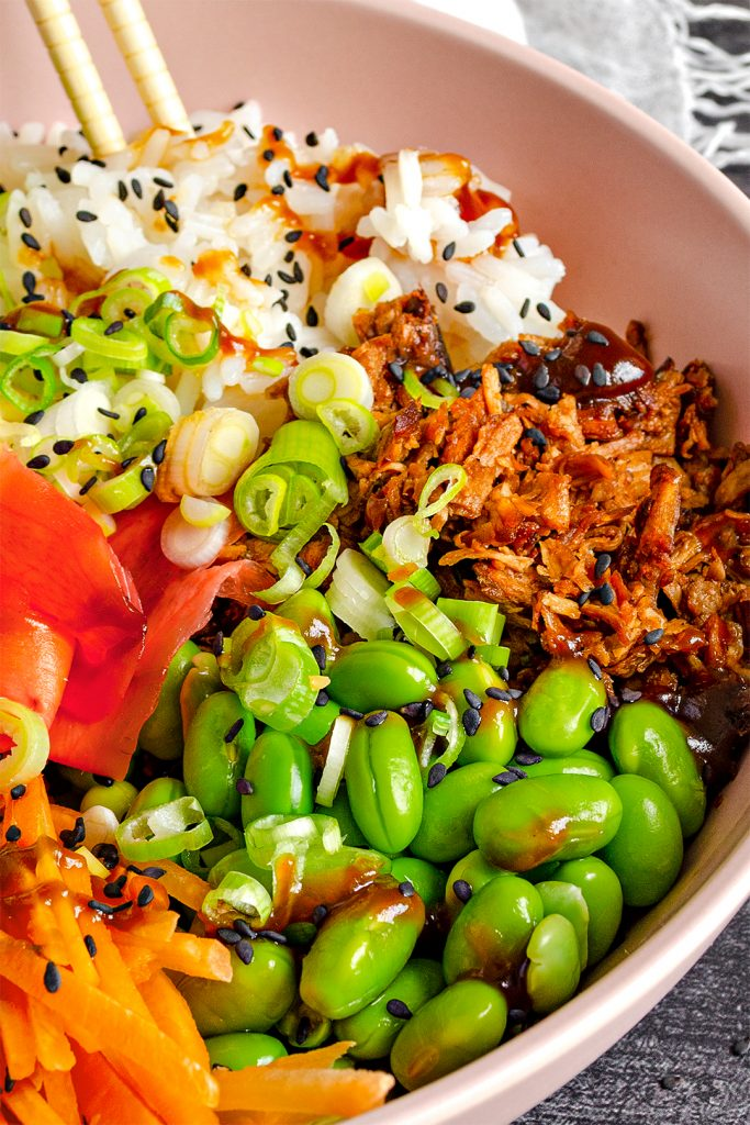 A vegan sushi bowl with rice, vegan shredded duck, edamame beans, carrot, cucumber, avocado, pink pickled ginger, sesame seeds, spring onions and hoisin sauce