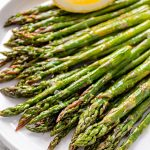 Close up of a plate of delicious lemony roasted asparagus