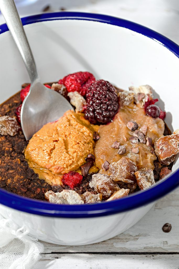Close up of chocolate, caramel and peanut butter baked oats in a bowl